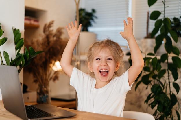 Ein kleines mädchen sitzt mit einem laptop an einem tisch und hebt die hände in die luft.