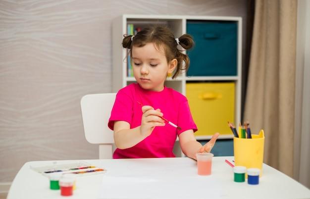 Ein kleines mädchen sitzt mit farben und pinseln an einem tisch