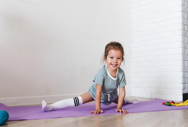 Ein kleines mädchen sitzt während eines fitnesskurses zu hause auf dem spagat