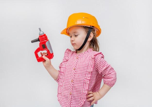 Ein kleines mädchen spielt einen baumeister. ein mädchen in einem orangefarbenen helm mit einem schraubenzieher.