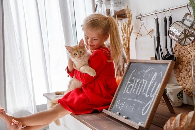 Ein kleines mädchen spielt mit einem kätzchen in der küche des hauses. das konzept einer menschlichen familie und eines haustieres