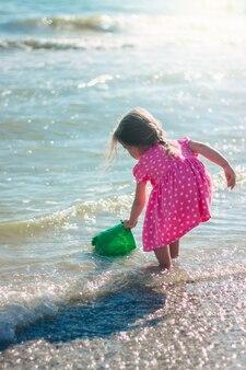 Ein kleines mädchen spielt mit einem schulterblatt und einem eimer am strand in einem rosa herzkleid