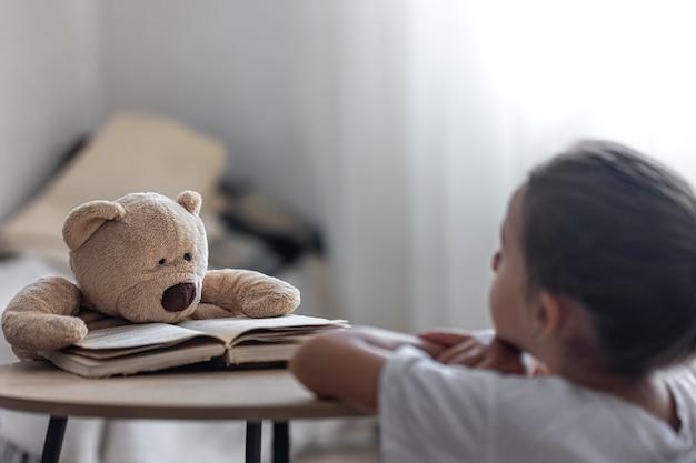 Ein kleines mädchen spielt mit ihrem teddybären und einem buch, bringt ihm das lesen bei, spielt in der schule.