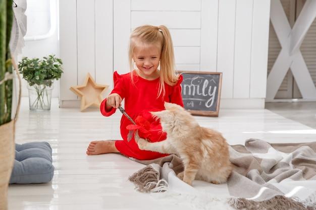 Ein kleines mädchen spielt mit kätzchen auf dem boden des hauses. das konzept einer menschlichen familie und eines haustieres