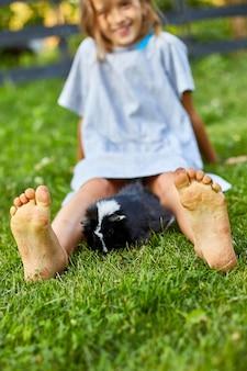 Ein kleines mädchen spielt mit schwarzem meerschweinchen, das im sommer im freien sitzt, pet calico meerschweinchen weidet im gras des hinterhofs seines besitzers, liebt haustiere