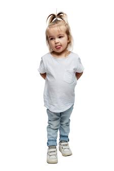 Ein kleines mädchen steht und zeigt ihre zunge. kind 4 jahre alt in jeans und einem weißen t-shirt. vollständige höhe. isoliert auf weißem hintergrund. vertikal.