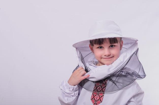 Ein kleines mädchen trägt einen bienenanzug im weißen studiohintergrund.