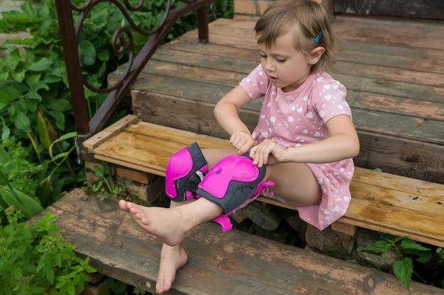 Ein kleines mädchen trägt schutz für rollschuhfahren auf den stufen ihres landhauses das konzept eines aktiven gesunden lebensstils und sicheren fahrens