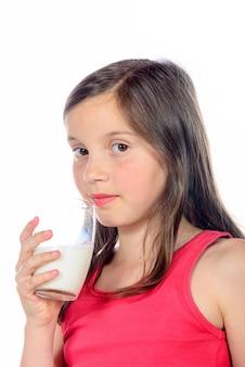 Ein kleines mädchen trinkt ein glas milch