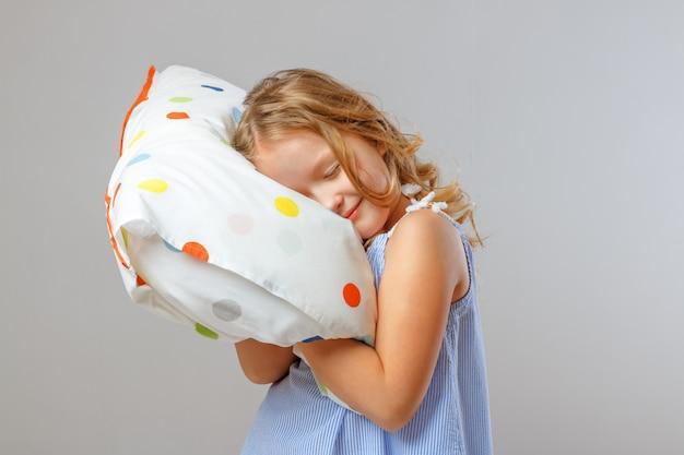 Ein kleines mädchen umarmt ein weiches kissen, schließt die augen und posiert vor einem studiohintergrund.