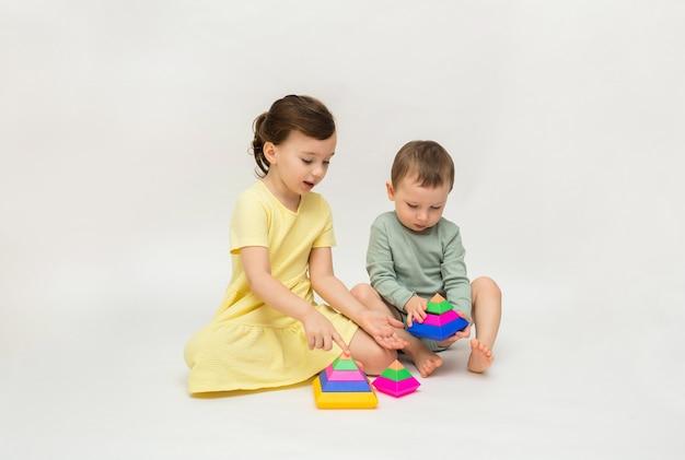 Ein kleines mädchen und ein junge spielen mit einer bunten pyramide auf einem weißen hintergrund