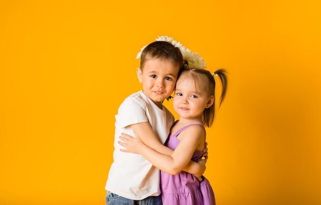 Ein kleines mädchen und ein junge umarmen sich auf einer gelben oberfläche mit platz für text