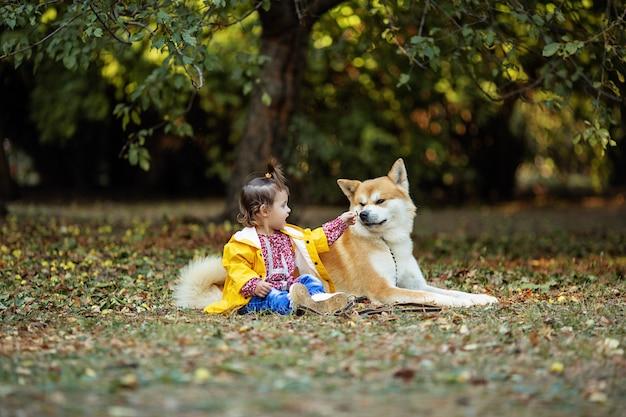 Ein kleines mädchen und ein roter hund sitzen im herbstpark