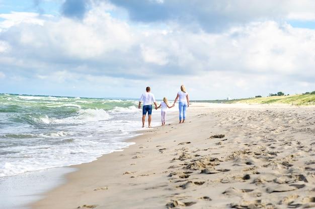 Ein kleines mädchen und ihre eltern gehen am strand an der ostsee in litauen spazieren.