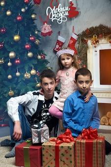 Ein kleines mädchen und zwei jungen sitzen in der nähe des baumes am kamin mit geschenken. drei glückliche kinder in der nähe des baumes am kamin mit geschenken. im hintergrund russische buchstaben wörter: frohes neues jahr.