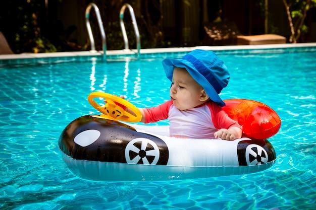 Ein kleines mädchen unter einem jahr fährt ein schlauchboot in form eines autos im pool