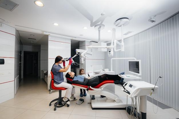 Ein kleines mädchen unterstützt ihre mutter bei der behandlung beim zahnarzt.