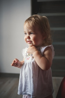 Ein kleines mädchen von 1,5 jahren steht und lächelt. das kind tanzt und geht. fröhliches mädchen in der wohnung