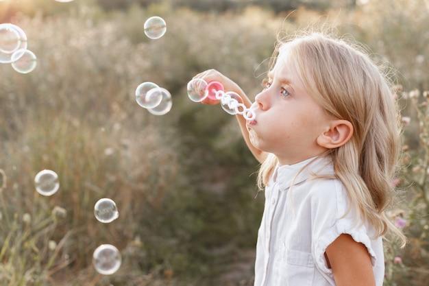 Ein kleines mädchen von 5 jahren macht bei einem spaziergang seifenblasen. sonniger tag