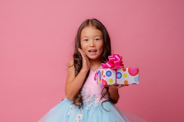 Ein kleines mädchen von asiatischem aussehen hält ein geschenk in ihren händen, das ihren geburtstag feiert