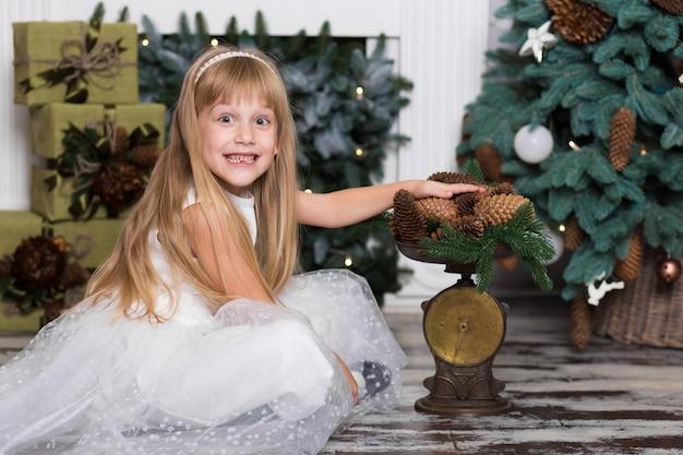 Ein kleines mädchen wiegt auf der waage tannenzapfen dekorationen für den weihnachtsbaum. frohe weihnachten und ein glückliches neues jahr. menschen und kinder