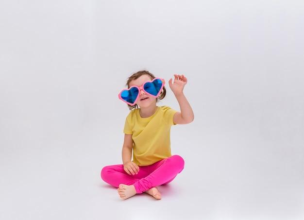 Ein kleines mädchen winkt mit einer großen sonnenbrille auf einem weißen raum mit einer kopie des raums. nettes kleines blondes mädchen sieht aus