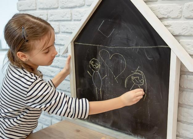 Ein kleines mädchen zeichnet eine kreidezeichnung auf eine tafel in form eines hauses.