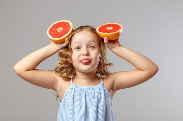 Ein kleines mädchen zeigt ihre zunge und ersetzt ihre ohren durch grapefruithälften.