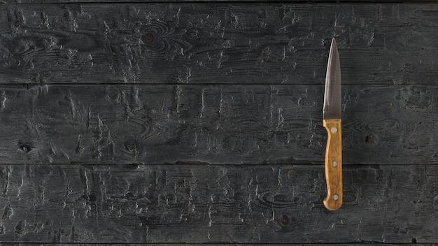 Ein kleines messer mit einem holzgriff auf einem dunklen holztisch. küchenzubehör.