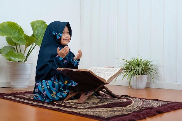 Ein kleines muslimisches mädchen betet mit ihrem koran zu hause auf dem gebetsteppich auf ramadan kareem
