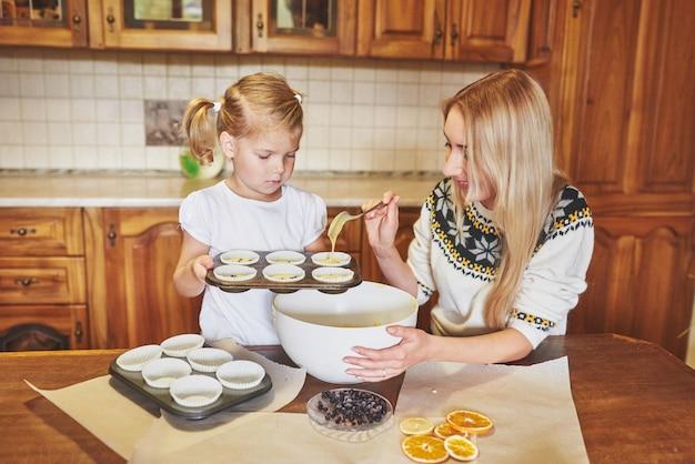 Ein kleines schönes mädchen bereitet cupcakes vor
