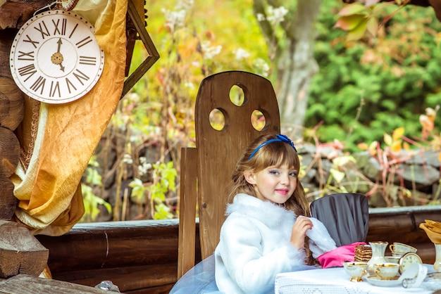 Ein kleines schönes mädchen, das zylinderhut mit den ohren hält, mögen ein kaninchen in den händen am tisch
