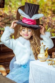 Ein kleines schönes mädchen, das zylinderhut mit den ohren hält, mögen ein kaninchen obenliegend am tisch