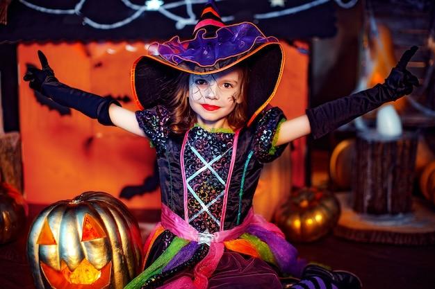 Ein kleines schönes mädchen in einem hexenkostüm feiert zu hause in einem innenraum mit kürbissen und pappmagiehaus auf dem hintergrund