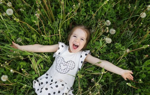 Ein kleines schönes mädchen liegt und lacht im gras auf einem frühlingsfeld im freien und genießt die natur. das konzept der freiheit