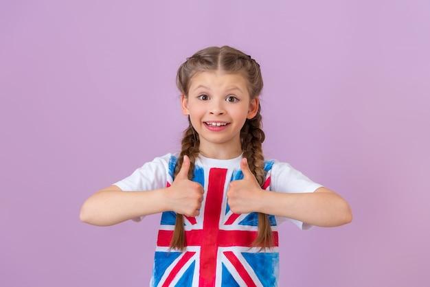 Ein kleines, schönes mädchen mit zöpfen auf einem isolierten hintergrund gab einen daumen nach oben. englische flagge auf dem t-shirt.