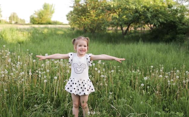 Ein kleines schönes mädchen steht und lacht im gras auf einem frühlingsfeld im freien und genießt die natur. das konzept der freiheit