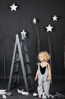 Ein kleines schönes lockiges Mädchen in der Nähe der Leiter auf einem grauen Hintergrund