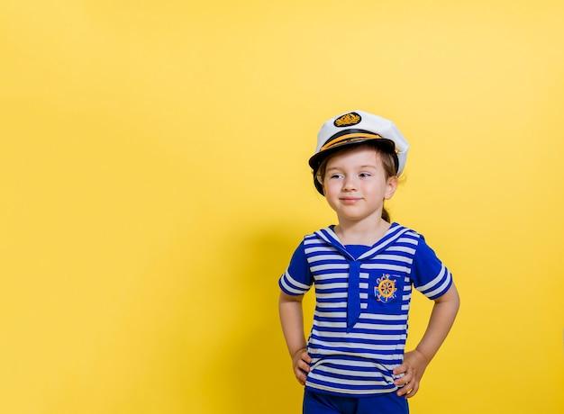 Ein kleines seemannsmädchen auf einem gelben platz schaut weg. ein mädchen in einem matrosenanzug und einer kappe auf einem isolierten raum mit kopierraum