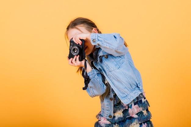 Ein kleines süßes mädchen, das foto auf einem gelben hintergrund macht.