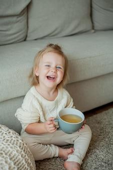 Ein kleines süßes mädchen in einem orangefarbenen pullover trinkt tee. gemütliches porträt eines girlsitting zu hause. fallen.