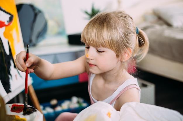 Ein kleines süßes mädchen malt zu hause auf einer staffelei ein großes bild mit acryl
