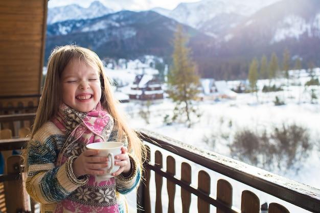 Ein kleines süßes mädchen trinkt tee über den winterbergen in zakopane, koscielisko, dem konzept der wintererholung