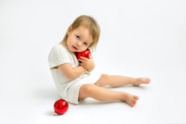 Ein kleines süßes mädchen umarmt eine rote weihnachtskugel aus glas