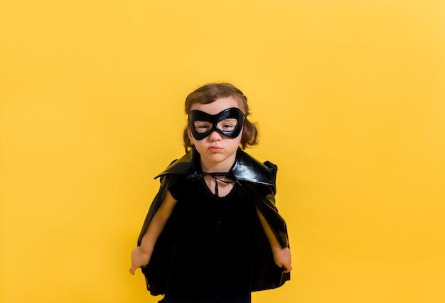 Ein kleines supergirl in einer schwarzen maske und cape auf einem gelben isoliert