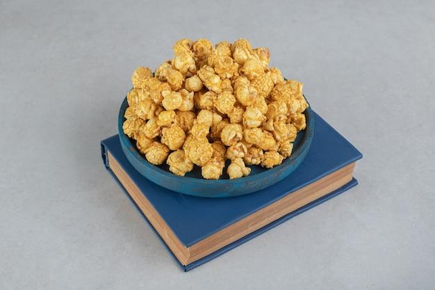 Ein kleines tablett mit karamellbeschichtetem popcorn auf einem buch auf marmor.