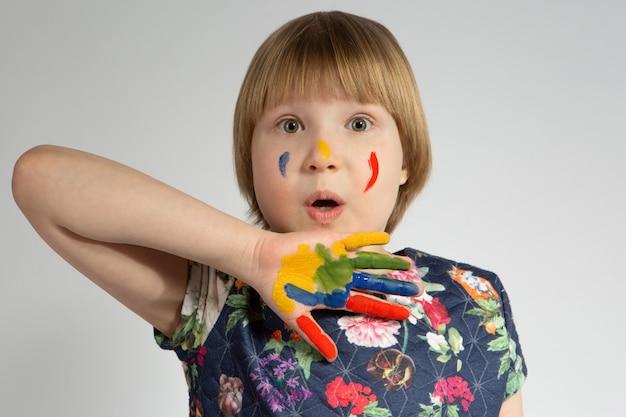 Ein kleines verängstigtes mädchen bedeckt ihr gesicht mit einer farbigen hand