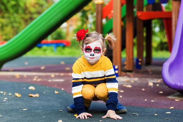 Ein kleines vorschulmädchen mit gemaltem gesicht, das auf dem spielplatz lächelt, feiert halloween oder den mexikanischen tag der toten.