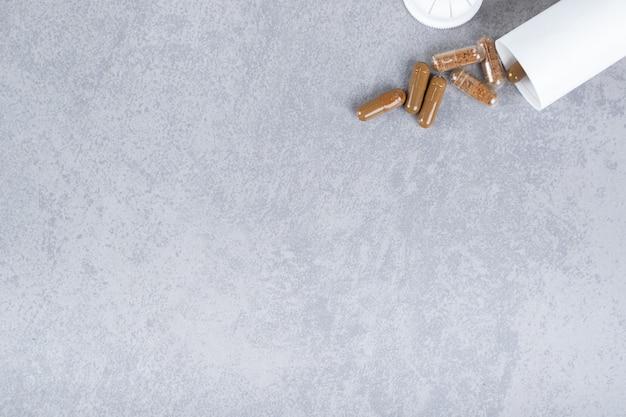 Ein kleines weißes glas mit braunen pillen auf grauer oberfläche