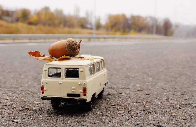 Ein kleines weißes spielzeugauto trägt eine eichel auf dem dach